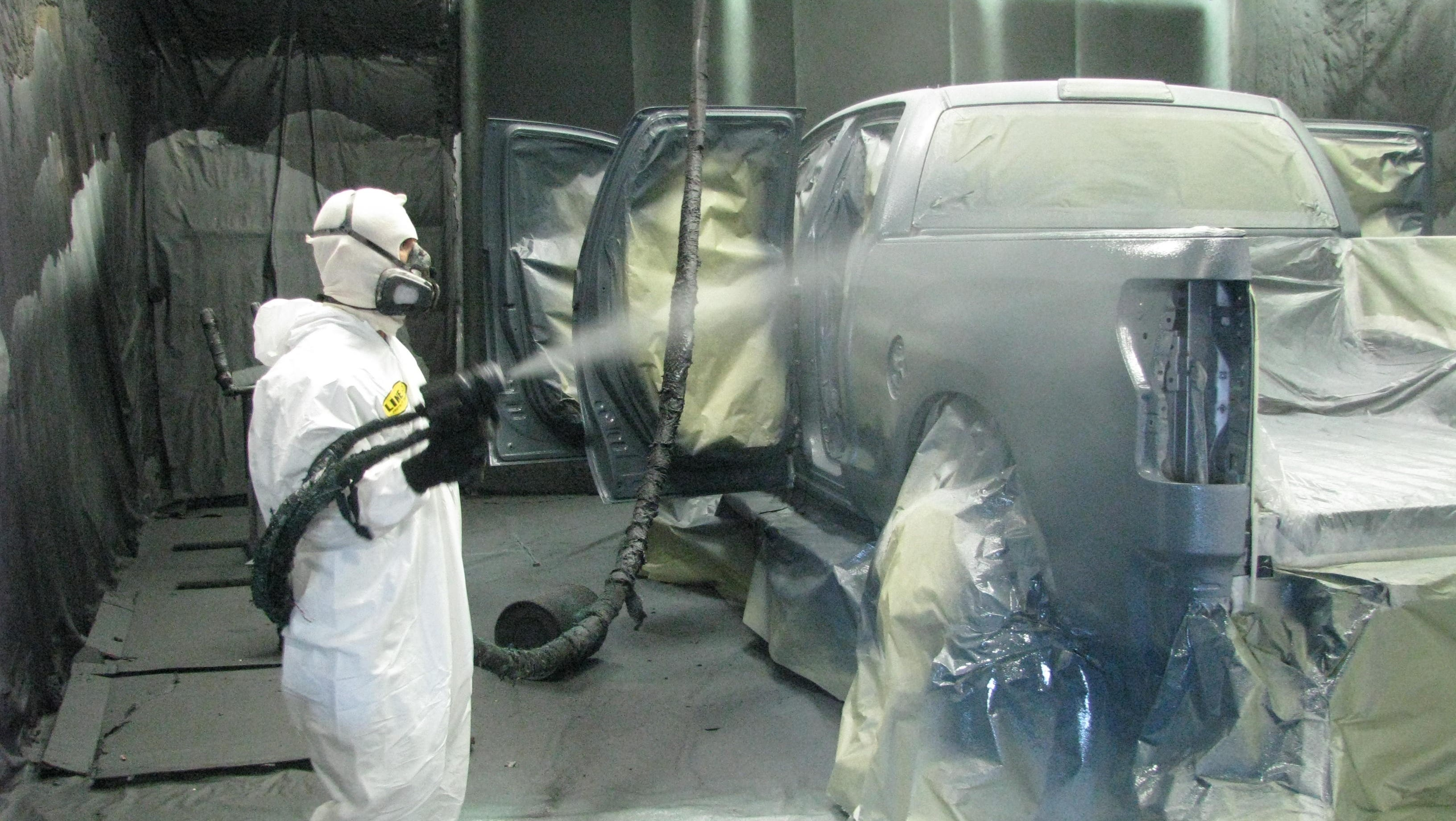 A professional doing a bedliner paint job