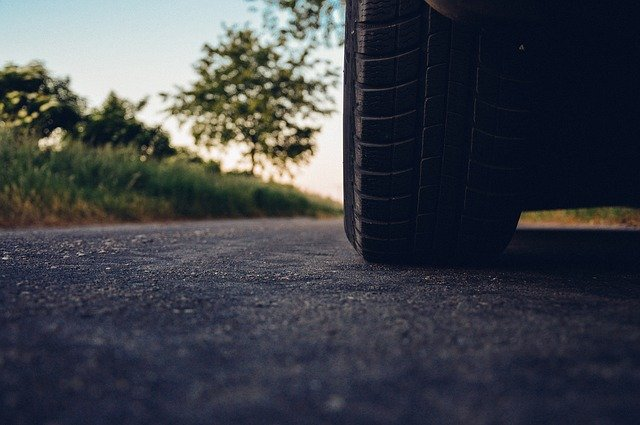 A photo of a car tire on the road
