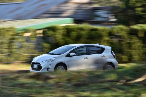 Toyota hybrid car running with the bushes blurred on background