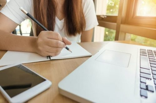 close-up of woman writing notes in front of laptop