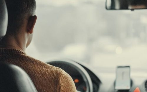 driver wearing brown sweater facing the driving wheel