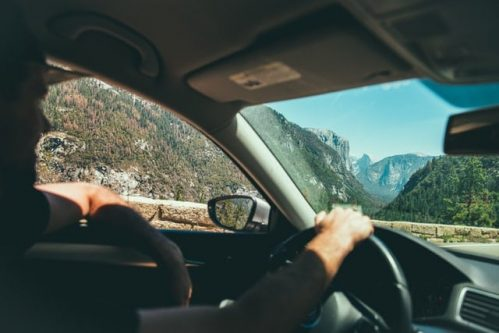 man driving with one arm on window