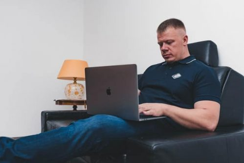 man in black polo sitting on couch while using a Macbook