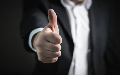 man in suit giving the thumbs up