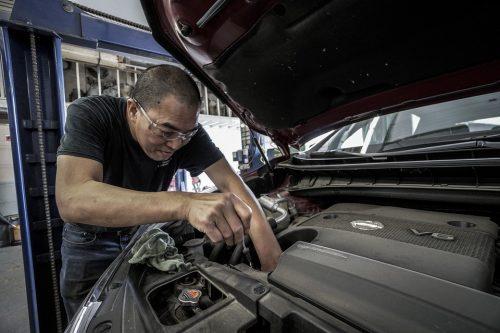 man with glasses and in black shirt repairing car