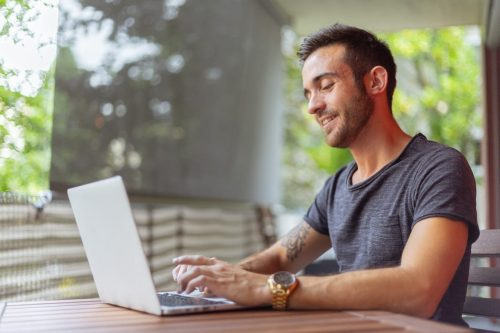 man with gray shirt typing on laptop