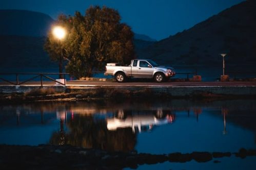 moving pickup truck with reflection on water
