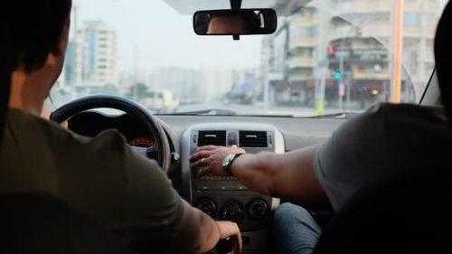 passenger holding driving wheel on the road