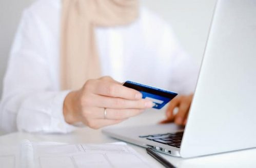 person with scarf holding card in front of laptop