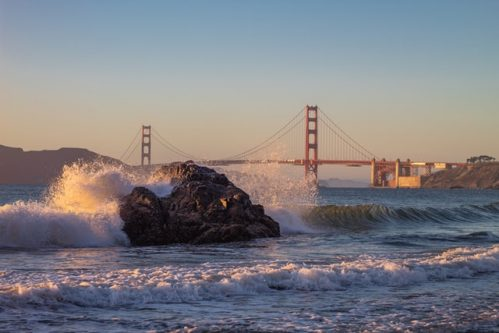 waves crashing against rock with the Golden Gate Bridge as background