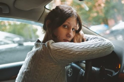 woman in brown sweater resting head on steering wheel